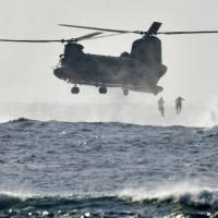 Self-Defense Forces personnel jump off a transport helicopter into the sea in Okinawa Prefecture as they conduct a joint rescue drill with the U.S. military on Monday morning. | KYODO