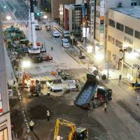 Repair work continues Saturday after a massive sinkhole opened up last week near Hakata Station in the city of Fukuoka. | KYODO