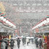 People walk along Nakamise-dori, an approach to Sensoji Temple, one of Tokyo's popular sightseeing spots, on Thursday morning amid the season's first snow in the capital. | KYODO