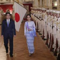 De facto Myanmar leader Aung San Suu Kyi, accompanied by Prime Minister Shinzo Abe, reviews a guard of honor before their meeting at the Government Guesthouse in Tokyo on Wednesday. | AFP-JIJI