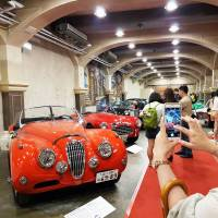 A visitor photographs vintage cars with her smartphone at an exhibition of vehicles in downtown Taipei on Saturday. | KYODO