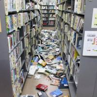 Books are seen falling from racks at a public library in the city of Iwaki, Fukushima Prefecture, on Tuesday morning. | KYODO