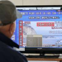 An evacuee watches news of tsunami warnings for Fukushima and Miyagi prefectures at a temporary shelter in Sendai on Tuesday morning, after a magnitude 7.4 earthquake shook the country's northeast. | KYODO