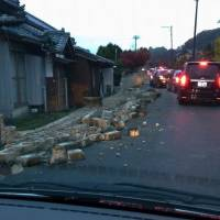 A traffic jam forms as people try to evacuate to higher ground in Iwaki, Fukushima Prefecture, at around 6:30 a.m. Tuesday, while toppled bricks lie strewn on the road. | KYODO