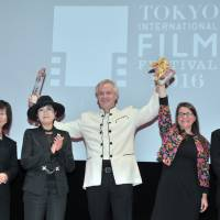 German director Chris Kraus (center) and producer Kathrin Lemme (second from right) celebrate after his film 'The Bloom of Yesterday' won the top prize at the Tokyo International Film Festival on Thursday, as Seiko Watch Corp. executive Hiromi Kanagawa (left), Tokyo Gov. Yuriko Koike (second from left) and chief juror Jean-Jacques Beineix look on. | YOSHIAKI MIURA