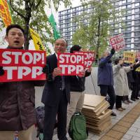 People demonstrate against the Trans-Pacific Partnership agreement in front of the Diet building in Tokyo on Wednesday morning. | TOMOHIRO OSAKI