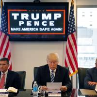 Then-Republican U.S. presidential candidate Donald Trump participates in a roundtable discussion on national security with retired army Gen. Michael Flynn (left) and retired army Lt. Gen. Keith Kellogg in New York in August. | AP