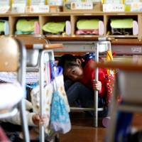 Schoolchildren take shelter under desks during a tsunami simulation drill ahead of World Tsunami Awareness Day at Futaba Elementary School in Choshi, Chiba Prefecture, last Friday. | REUTERS