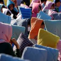 Schoolchildren wearing padded hoods to protect them from falling debris gather in an evacuation shelter at Futaba Elementary School in Choshi, Chiba Prefecture, last Friday. | REUTERS