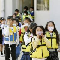 Elementary school pupils converge on a playground in the city of Wakayama last Thursday in an annual drill ahead of World Tsunami Awareness Day. | KYODO