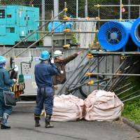 Police Wednesday investigate the area near the entrance of an industrial water tunnel in Kudamatsu, Yamaguchi Prefecture, where nine workers were hospitalized because of carbon monoxide poisoning. | KYODO