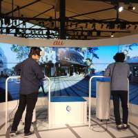 People try out KDDI's virtual traveling service on Nov. 2 in Tokyo. Wearing headsets, the two people are vicariously exploring Manly Beach, Australia, in real time, seeing what a travel agent sees on the screen around them. | KAZUAKI NAGATA