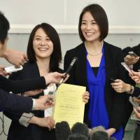 Hiroko Masuhara (left) and Koyuki Higashi display a piece of paper acknowledging receipt of their application for recognition of their relationship at Tokyo's Shibuya Ward office in October 2015. | KYODO
