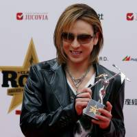 Getting credit: Yoshiki shows off his trophy at the 2016 Classic Rock Roll of Honour awards in Tokyo on Nov. 11. | REUTERS