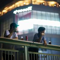 Friends enjoy a late-night drink on an overpass. | ANDREW CURRY