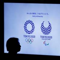 Into the shadows: A woman is silhouetted against a monitor showing Tokyo 2020 Olympic and Paralympic emblems during the Olympic and Paralympic flag-raising ceremony at the Tokyo Metropolitan Government in Tokyo on Sept. 21. | TORU HANAI / REUTERS