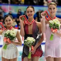 Russia's Anna Pogorilaya (center) is joined by NHK Trophy runner-up Satoko Miyahara (left) and compatriot Maria Sotskova for a group photo after her triumph in Sapporo on Saturday. | AFP-JIJI