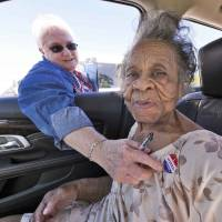 Grace Bell Hardison, a 100-year-old woman recently mentioned by U.S. President Barack Obama after attempts were made to purge her from the voter registration list and hence deny her right to vote, receives an 'I Voted Today' sticker from an election official in Belhaven, North Carolina. | REUTERS