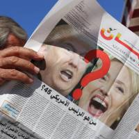 A man reads an edition of Iraqi daily newspaper Azzaman, bearing images of Donald Trump and Hillary Clinton. | AFP PHOTO
