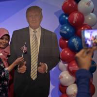 A woman takes a photo with a cutout of Donald Trump at the U.S. embassy in Jakarta, Indonesia.
