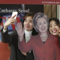 South Korean students take photos with a cutout of Hillary Clinton. | AP PHOTO