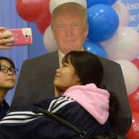 Vietnamese students take photos with a paper replica of Donald Trump. | AFP PHOTO