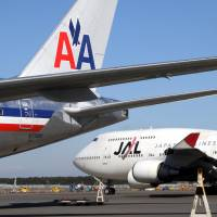An American Airlines jet sits next to a Japan Airlines plane at Narita International Airport in Chiba Prefecture. | BLOOMBERG
