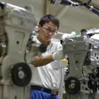 A worker assembles engine blocks at the General Motors assembly plant in Wuhan in central China's Hubei province in 2014. Shares of General Motors fell Wednesday after a Chinese state-run newspaper reported that the government will penalize an unidentified U.S. automaker soon for alleged anti-competitive behavior. The China Daily didn't identify the company but quoted the government's top price regulator as saying the automaker would be fined for 'impeding competition.' | CHINATOPIX VIA AP, FILE