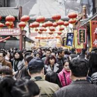 Shoppers walk past stalls at a street market in Beijing. | BLOOMBERG