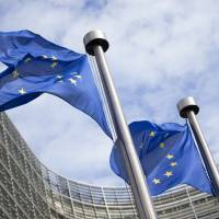Flags of the European Union fly outside the European Commission building in Brussels. | BLOOMBERG