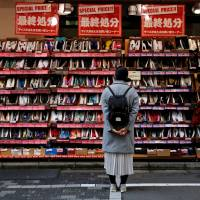 A woman looks at shoes on sale at an outlet store in Tokyo on Dec 1. The capital jumped up from 12th last year, while Yokohama and Osaka joined the top 10, ECA International said Wednesday in a report comparing the global cost of living for expatriates. | REUTERS