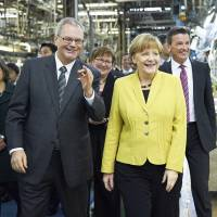 Albert Kirchmann (left) shows Mitsubishi Fuso Truck and Bus Corp.'s Kawasaki factory to German Chancellor Angela Merkel in March 2015. | COURTESY OF MITSUBISHI FUSO TRUCK AND BUS CORP.