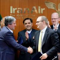 Farhad Parvaresh (left), chairman and managing director of IranAir, seals the deal with Fletcher Barkdull, Boeing regional director, after signing an agreement in the presence of Abbas Ahmad Akhoundi, minister of roads and urban development, in Tehran on Sunday. | AFP-JIJI
