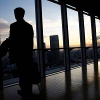 An IT engineer who wishes to remain anonymous poses by the window of a Tokyo office building after being interviewed by Reuters on Dec. 7. | REUTERS