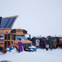 A procession makes its way down to the Cannonball River to take part in a Native American water ceremony at the Oceti Sakowin camp where people have gathered to protest the Dakota Access oil pipeline in Cannon Ball, North Dakota, Thursday. | AP