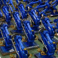 Yaskawa Electric Corp.'s Motoman robots await shipment at the company's factory in Kitakyushu in July 2015. | BLOOMBERG