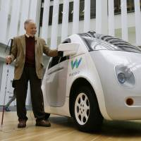 Steve Mahan, who is blind, stands by a Waymo driverless car during a Google event held Dec. 13 in San Francisco. Driverless vehicles may one day help people with visual impairments to travel by themselves. | AP