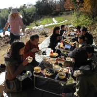 Three families enjoy a meal featuring vegetables grown with no agrochemicals on a hillside in the Tokyo suburb of Machida, at a farming-experience event this month organized through the sharing economy service TABICA. | KYODO