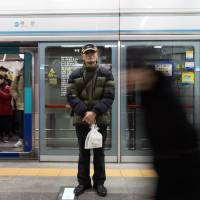 Poverty turns Seoul seniors into subway couriers