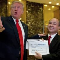 President-elect Donald Trump and SoftBank CEO Masayoshi Son speak to reporters at Trump Tower in New York on Tuesday. | AP