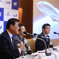 Hideo Sawada (left), chairman and CEO of H.I.S. Co., speaks as Shuji Ogawa (center), CEO of PD Aerospace Ltd., and Shinya Katanozaka, president and CEO of ANA Holdings Inc., look on during a news conference in Tokyo on Thursday. | BLOOMBERG