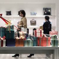Christmas decorations sit in a window display as shoppers browse in a luxury handbag and shoe store in the Marunouchi area of Tokyo on Dec. 19. | BLOOMBERG