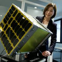 Astroscale Japan Inc. President Miki Ito poses with a model of the company's IDEA OSG 1 micro-satellite at her office in Tokyo on Dec. 5. | REUTERS
