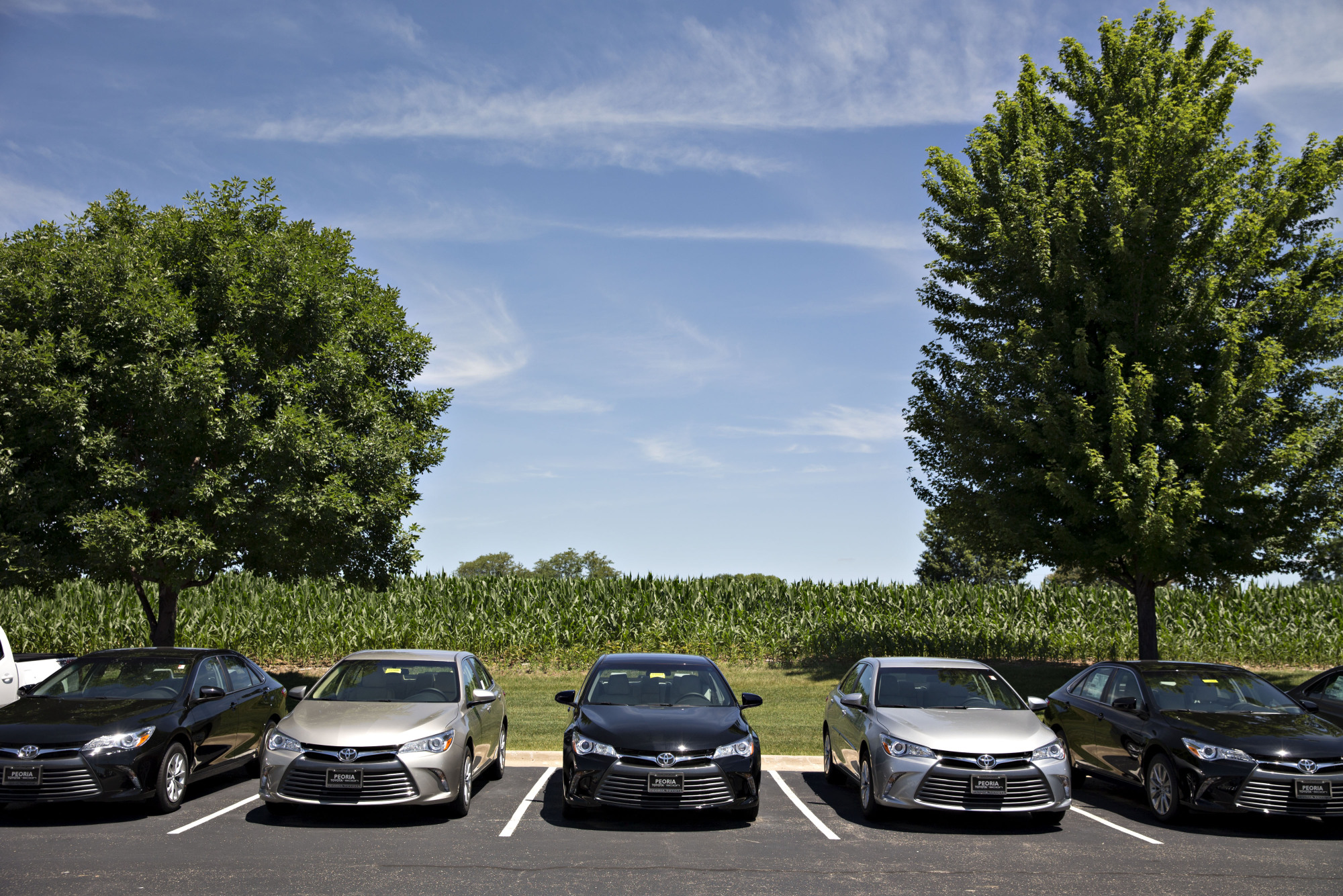 A row of 2016 Toyota Motor Corp. Camry vehicles sit on display for sale at a Toyota car dealership in Peoria, Illinois, in June. Toyota plans to unveil a redesigned Camry next month.   BLOOMBERG