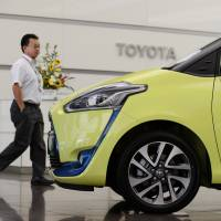 A man walks past a Toyota Sienta displayed at the company's head office in Tokyo. | BLOOMBERG