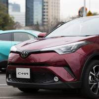 The Toyota C-HR gasoline model (right) and hybrid model SUVs are displayed in a parking lot during a media event ahead of the sales launch in Tokyo on Dec. 13. | BLOOMBERG