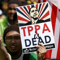 Protesters wave placards at a demonstration against the Trans-Pacific Partnership in Kuala Lumpur in January. | REUTERS