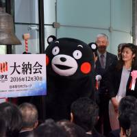 Kumamon, the iconic mascot of Kumamoto Prefecture, rings the closing bell at the Tokyo Stock Exchange on Friday to end the year's trading as four-time Olympic gold medalist wrestler Kaori Icho looks on. | SATOKO KAWASAKI