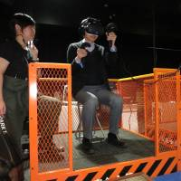 A man tries a virtual reality game called 'Dive Hard' in which the player scales a skyscraper and fights robots at a media preview of new VR arcade in Tokyo's Shibuya Ward on Wednesday. | KAZUAKI NAGATA
