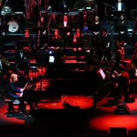 Classic concert: Yoshiki sits at a piano and performs with Katie Fitzgerald of Violet UK, a Yoshiki side project.